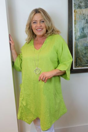 Woman is wearing V neck linen top Tessie by Kasbah Clothing in Lime