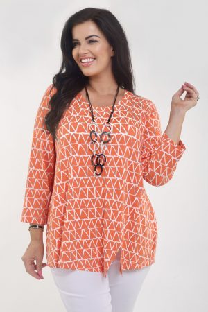 Model is wearing patterned jersey tee in papaya and cream triangles by Q'Neel
