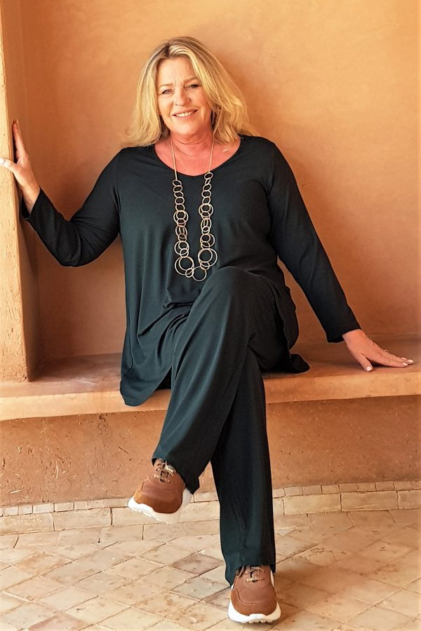 Model is wearing Paige jersey palazzos in forest green by kasbah Clothing